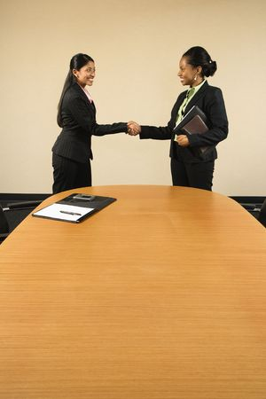african american handshake: Two businesswomen in suits shaking hands and smiling.
