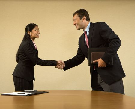 Two businesspeople in suits shaking hands and smiling. Stock Photo