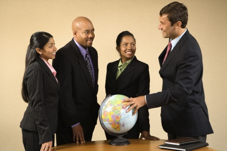 imports: Corporate businesspeople standing around world globe smiling and talking.