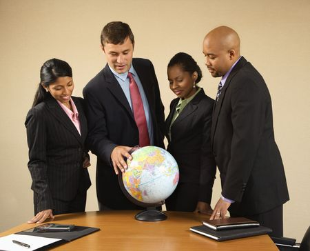 Corporate businesspeople standing around world globe smiling and talking. photo