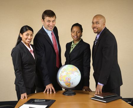 outsource: Corporate businesspeople standing around world globe smiling.