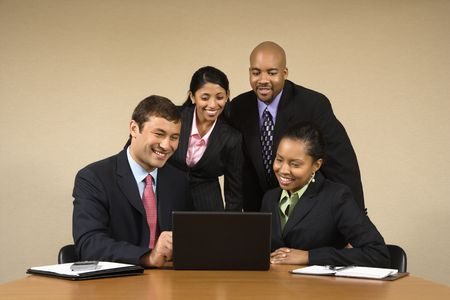 Businesspeople gathered around laptop computer looking at monitor and smiling. Stock Photo - 2115298