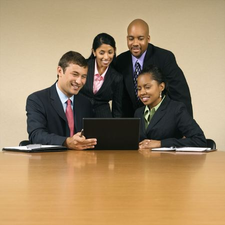 Businesspeople gathered around laptop computer looking at monitor and smiling.