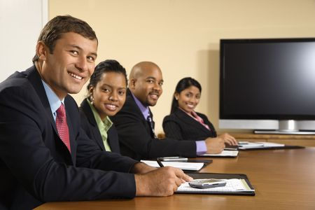 Businesspeople sitting at conference table smiling with flat screen display in background. Stock Photo - 2115217