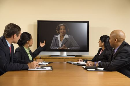 Businesspeople sitting at conference table looking at flat screen display. photo