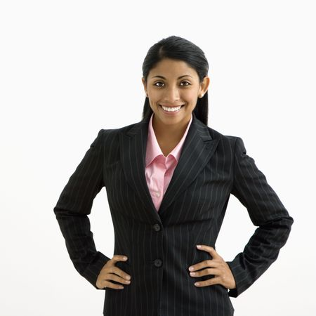 empowered: Portrait of smiling businesswoman with hands on hips against white background. Stock Photo