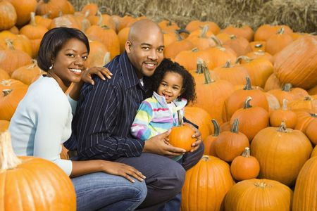 Parents and daughter picking out pumpkin and smiling at outdoor market. Stock Photo