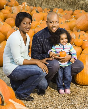 Parents and daughter picking out pumpkin and smiling at outdoor market. photo