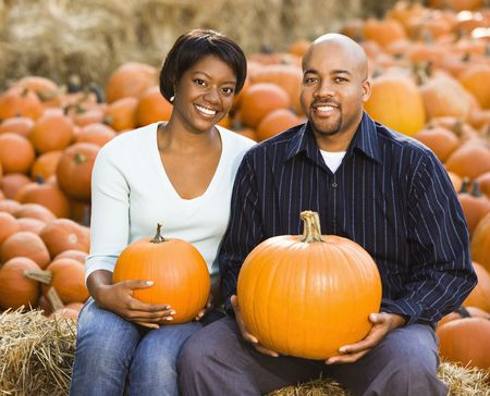 Happy smiling couple sitting on hay bales and holding pumpkins. photo