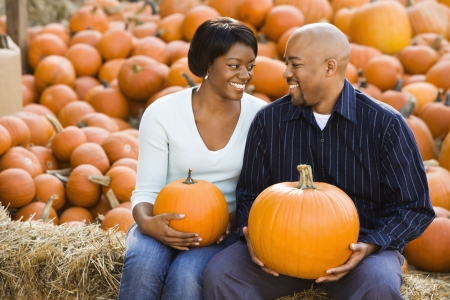 Happy smiling couple sitting on hay bales and holding pumpkins at outdoor market. photo