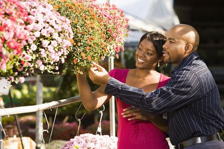 garden center: Happy smiling couple picking out flowers at outdoor plant market.