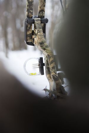 Camouflage bow and arrow with blurred foreground. photo