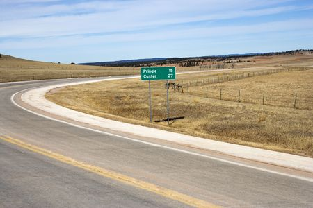 mileage: Winding road in South Dakota with mileage distance road sign.