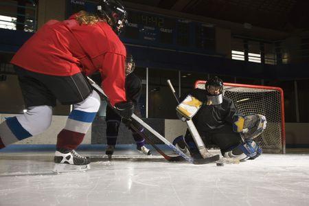 delito: Cauc�sicos jugador de hockey femenino tratando de hacer como portero objetivo protege la red.  Foto de archivo
