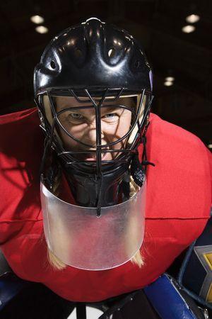 intimidating: Woman hockey goalie wearing helmet sneering looking intimidating. Stock Photo
