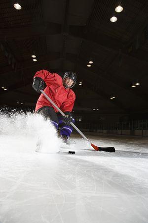 ice rink: Caucasian woman hockey player sliding kicking up ice.