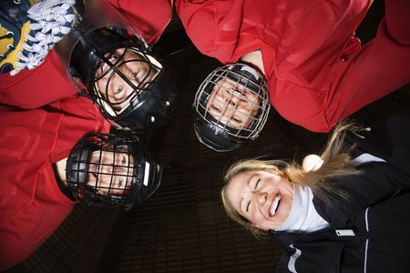 Low angle of female hockey players in huddle with coach smiling. Stock Photo