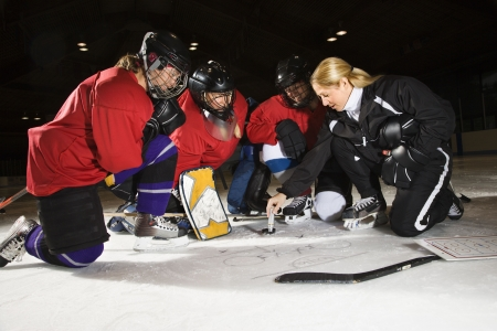 coach sport: Women hockey players on ice looking at game plan with coach. Stock Photo