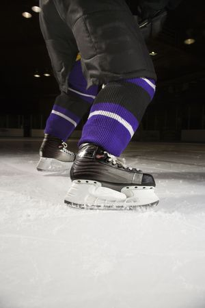 Low angle of hockey players legs and skates on ice rink.