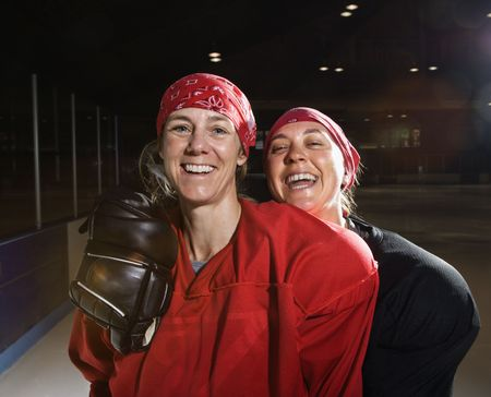 Women hockey players in uniform posing with helmets off on ice rink. photo