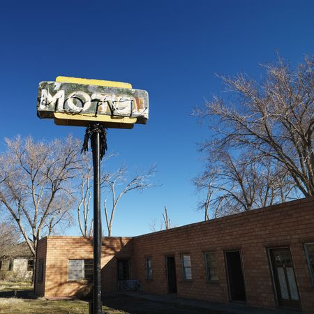 Rundown motel building with blue sky in background. photo