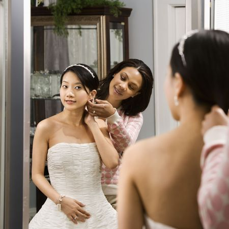 African-American woman helping Asian bride with hair. photo