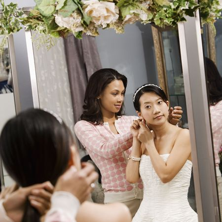 African-American woman helping Asian bride with hair. Stock Photo - 2145539