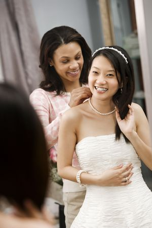African-American friend helping place necklace on Asian bride. photo