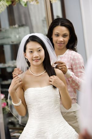 African-American friend holding Asian brides veil. photo