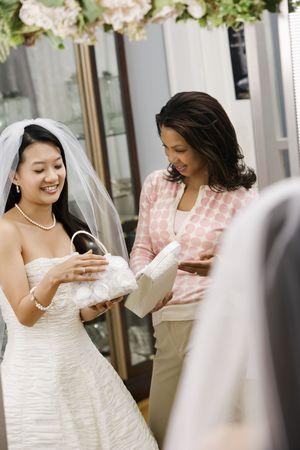 African-American mujer ayudar a Asia novia seleccionar el bolso.  Foto de archivo - 2145620