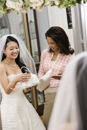 African-American woman helping Asian bride pick out handbag. photo