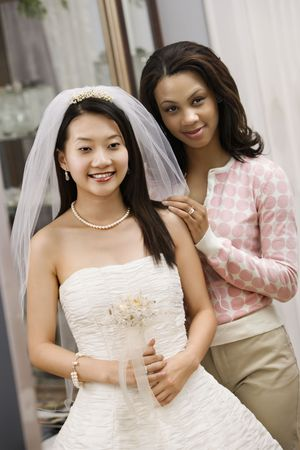 Asian bride and African-American friend admiring dress in mirror. photo