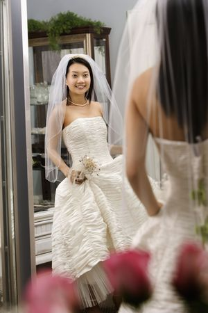 Asian bride admiring dress in mirror. photo