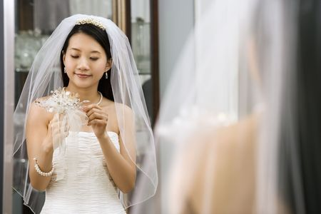 horizontals: Asian bride looking at bouquet in mirror.
