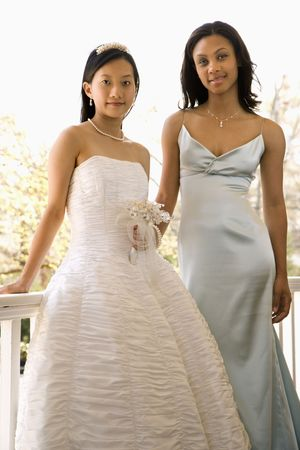 A portrait of a African-American maid of honor and Asian bride leaning against railing. Stock Photo - 2145551