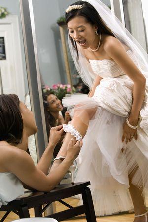 African-American bridesmaid placing garter on Asian brides leg. photo