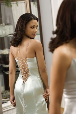 with reflection: Attractive African-American woman wearing evening gown looking in mirror.