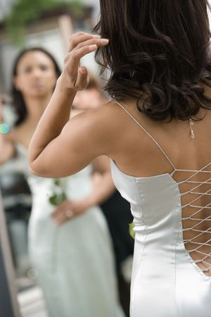 evening gown: Back of African-American woman in evening gown looking at mirror.
