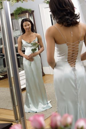 evening gown: Portrait of an African-American woman in a elegant evening gown looking in mirror. Stock Photo