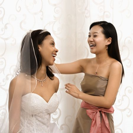 Asian bridesmaid laughing with African-American bride. photo