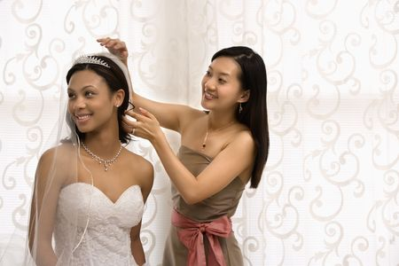 Asian bridesmaid adjusting veil of African-American bride. photo