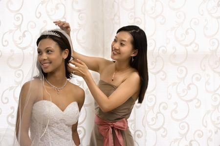 africanamerican: Asian bridesmaid adjusting veil of African-American bride.