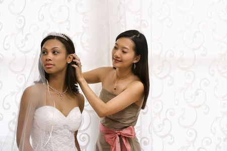 Asian bridesmaid fixing African-American bride's hair. photo