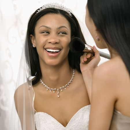 Asian bridesmaid applying makeup to African-American bride. photo
