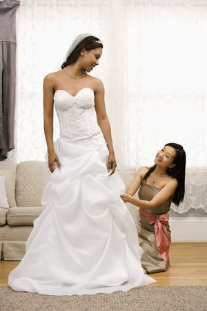 Asian bridesmaid fixing African-American bride's dress. photo