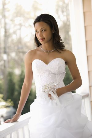 Portrait of African-American bride leaning against railing. photo