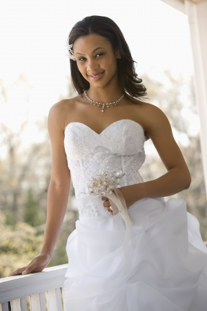 africanamerican: Portrait of African-American bride leaning against railing. Stock Photo