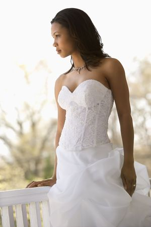 Portrait of African-American bride leaning against railing. Stock Photo