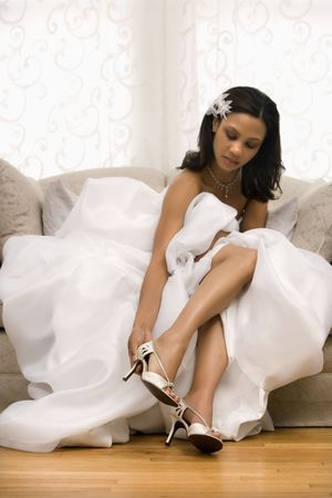 bridal gown: African-American bride placing shoe on foot.