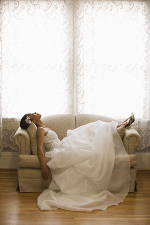 africanamerican: African-American bride lying on love seat. Stock Photo